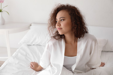 Morning of beautiful African-American woman in bedroom