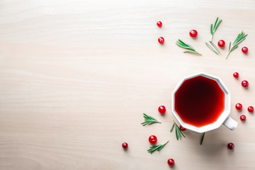 Flat lay composition with cup of red tea and cranberries on light background