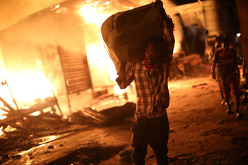 A man carries a sack out of a fire at a market in Port-au-Prince