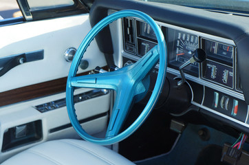 Fragment retro car dashboard. White leather and blue steering wheel.