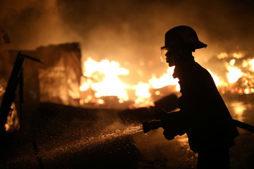 A firefighter works to extinguish a fire at a market in Port-au-Prince