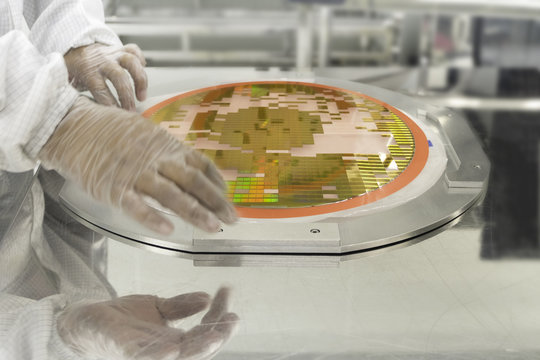 Motion blur picture of hand moving, hand engineer with white gloves sorting a silicon wafers from production in semiconductor hi-tech industry, blur background