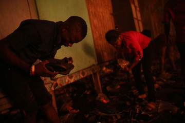 People look for goods during a fire at a market in Port-au-Prince
