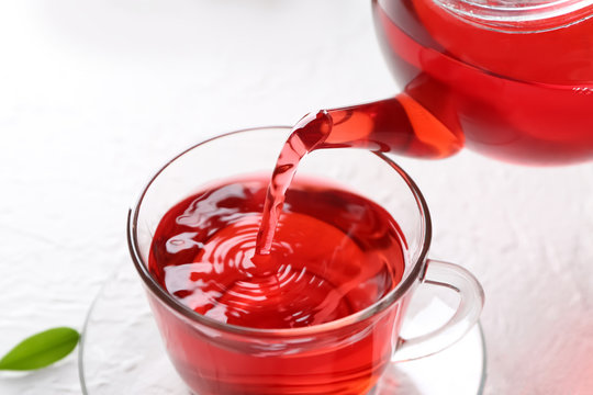 Pouring hot red tea into glass cup on table