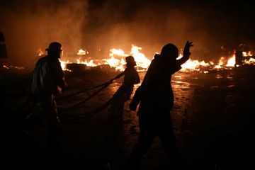 Firefighters work to extinguish a fire at a market in Port-au-Prince