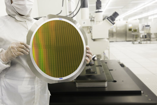 hi-tech industry: Engineer holding a silicon wafers with white gloves for inspection after grinding and die saw, a silicon wafers reflecting different colors or colorful glowing light