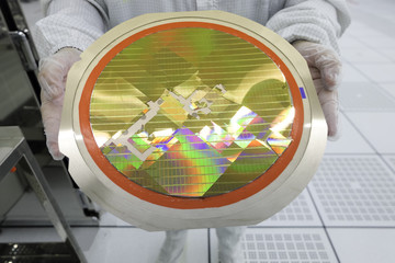 Wall Mural - engineer holding a silicon wafers broken from machine operation,working at clean room laboratory ,semiconductor ,image reflect light rainbow colours