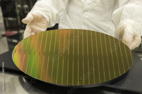 Wall mural engineer hands in white gloves holding silicon wafers showing detail of a silicon wafers reflecting colors ,  blurred background