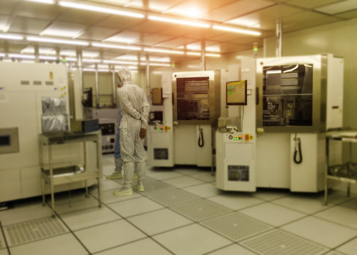 image not clear of technician in clean suits he is teaching a new technician in a semiconductors manufacturing facility ,select focus ,blurred background