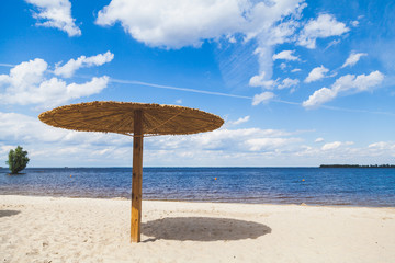Sunshade on sandy beach on summer day
