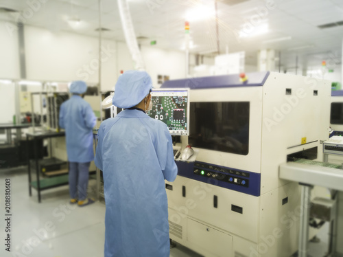 Rear view of worker supervises the visual inspection on automated