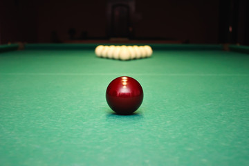 Closeup shot of red ball going in billiard pocket