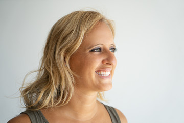 Side view of happy joyful blonde lady. Closeup of smiling attractive Caucasian woman in casual wear looking aside. Positive feelings and euphoria concept