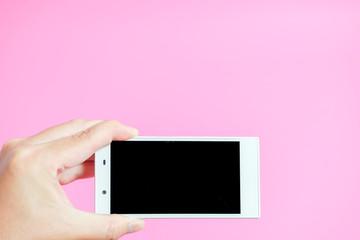 Close-up of using smartphone スマートフォンを使っている様子のクローズアップ ピンク色背景
