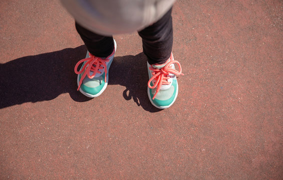 Top view of little girl legs with sneakers and black leggins training outdoors