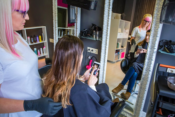 Beautiful young woman showing hairstyle photo in her smartphone to the hairdresser