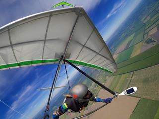 Hang glider pilot soar the thermal updrafts high over terrain