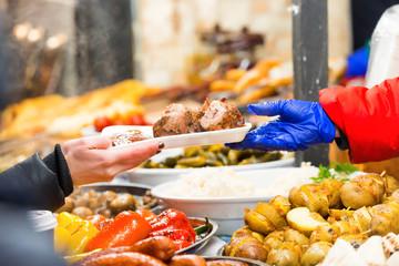 Hands of vendor serving food on street food market