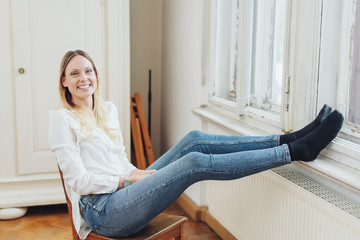 Smiling young woman relaxing with feet up