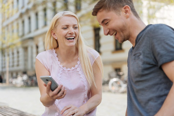 Laughing couple looking at data on a mobile