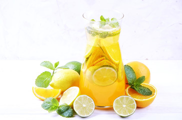 Two glasses & pitcher bottle of homemade refreshing lemonade with slices of organic ripe lemon, orange and lime, mint & ice on rustic white wooden table background. Close up, top view, copy space.