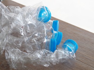 Plastic drinking water bottle Twisted on the wood table before dropping it to the trash. To reduce the storage space. Before entering the recycling process