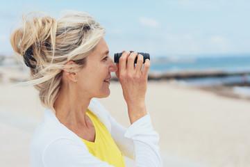 Attractive blond woman using binoculars