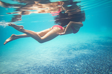 Asian women are diving at the pool. She was wearing a bikini