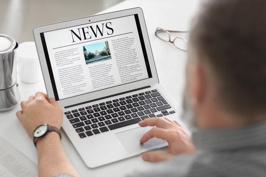 Senior man reading news on laptop screen at home