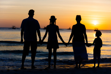 Silhouette of happy family having fun on the beach at the sunset time.