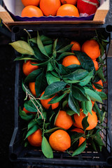 Bunch of fresh tangerines oranges in a box on market, top view. Oranges Background