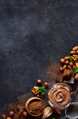 Black food background with cocoa, nuts and chocolate paste. top view