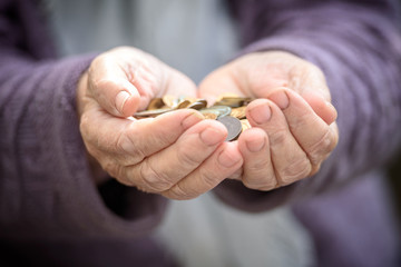 Money, coins, the grandmother on pension and the concept of life, minimum - in hands old a handful of coins. Close up