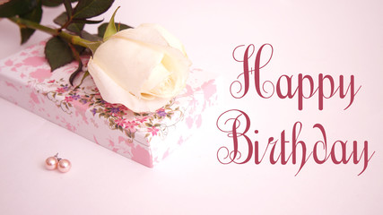 """greeting card with the words """"happy birthday"""", white rose, box and earrings"""