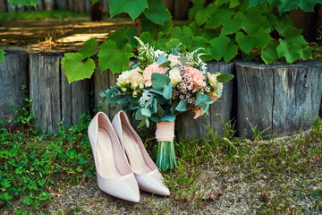 Beautiful wedding bouquet of pink and white roses and beige shiny bride shoes outdoors, copy space. Wedding morning preparation. Wedding bride accessories. Bridal bouquet and shoes