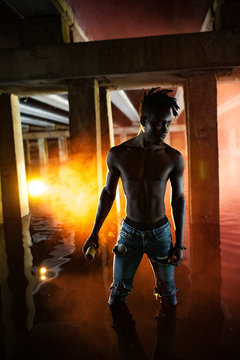 Young African man stands under bridge and holds colored red and yellow smoke bomb in his hands.
