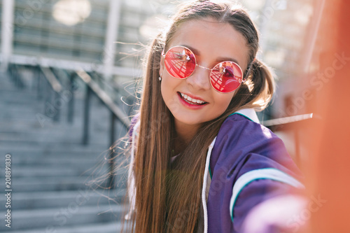 99bf3d22e110e Brightly beautiful young woman with collected light-brown hair wears pink  fashion glasses making selfie