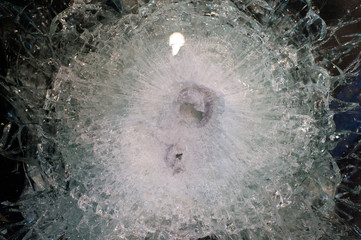 Bulletproof glass after gunshot, close up. Bulletproof glass destroyed or broken after shooting. Safety and protection concept. Bullets trace on armored glass
