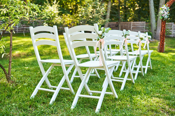 White wedding chairs with fresh flowers on each side of archway outroods, copy space. Empty wooden chairs for guests on green lawn in the garden prepared for wedding ceremony