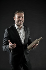 Man with bristle look cheerful and hospitably. Hospitality concept. Man on happy face posing with bottle of expensive alcohol. Businessman or man in formal suit cheerfully welcomes on dark background
