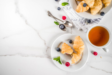 Sweet summer dessert, homemade baked mini croissants with berry jam, served with tea, fresh raspberries, blueberries and mint. On a white marble table, copy space top view
