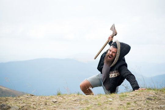 Man with beard on shouting face conquers top of mountain with axe, sky background. Survive in wild nature concept. Hipster with axe surviving in mountains. Guy brutal and bearded in wild nature