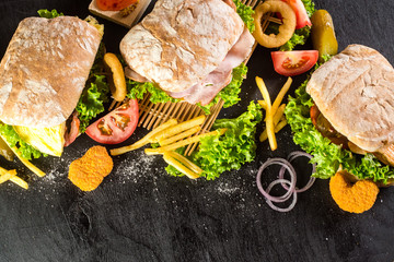 A few sandwiches or paninies with vegetables, french fries on black background. Top view. Copy space
