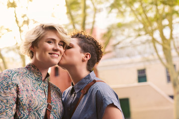 Young woman kissing her smiling girlfriend on the cheek