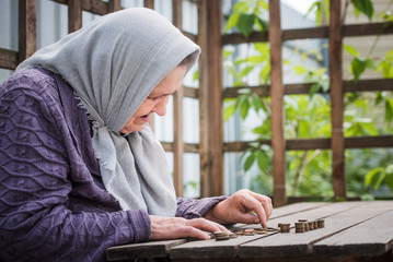 Money, coins, retired grandmother and the concept of a living wage - the Old woman sadly finds little money