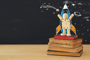rocket and space sketches with wooden dummy in front of classroom blackboard.