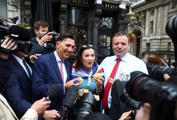 Arron Banks and Andy Wigmore, who ran the Leave.Eu pro-Brexit referendum campaign, eat pork pies offered by an anti-Brexit campaigner as they arrive to give evidence to the Digital Culture Media and Sport Parliamentary Committee in London