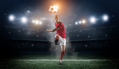 Soccer player in action on stadium background. Wall mural