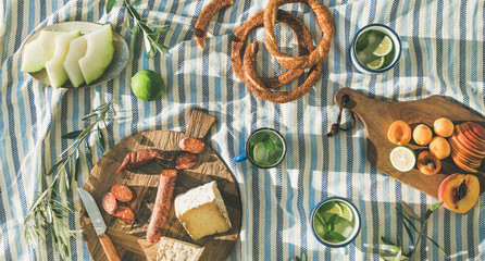 Zelfklevend Fotobehang Picknick Flat-lay of summer picnic set with fruit, cheese, sausage, bagels and lemonade over striped blanket, top view