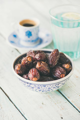 Traditional muslim food for Ramadan iftar meal. Dates in bowl, glass of water and coffee over wooden table.